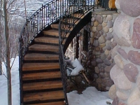41-0040-iron-anvil-stairs-grand-circular-treads-angle-iron-wood-steps-park-city-1